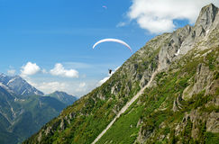 Paraglider flys in the mountains Royalty Free Stock Photo