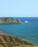 Paraglider glides over sea Royalty Free Stock Photo
