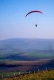 Paraglider i himlen, med rött canapy, ladscape av fält belo Arkivfoto