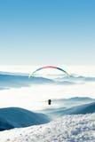 Paraglider i himlen ovanför en snöig lutning av ett berg Royaltyfri Bild
