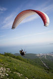 Paraglider jumps from the mountain to the sea, blue sky, warm breeze, a parachute, Stock Images