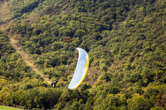 Paraglider landing. Paraglider with trail smoke against a blurred forest background (panning Stock Image