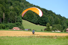 Paraglider landing in a field Stock Image