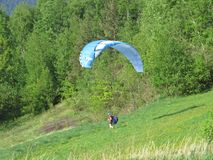 Paraglider Landing on Green Grass Ground after a Flight royalty free stock images