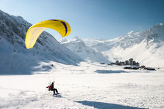 Paraglider landing on skis Royalty Free Stock Image
