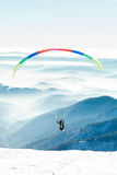 Paraglider launched into air from a mountain peak. Paraglider launched into air from a snowy slope of a mountain peak Royalty Free Stock Images