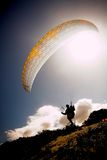 Paraglider launching from the. Ridge with a yellow and white canopy and the sun from behind. The paraglider is a silhouette and the shot is taken right after Stock Photos