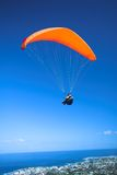 Paraglider launching. From the ridge with an orange canopy against a blue sky. The town of Hermanus (Western Cape, South Africa) in the bottom of the image Stock Photo