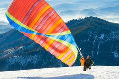 Paraglider launching into air from the very top of a snowy mountain slope Royalty Free Stock Images