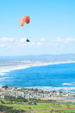 Paraglider. Launching from the ridge with a yellow and white canopy. The shot is taken right after takeoff. The canopy wingtip is sharp, with slight movement on Stock Photos