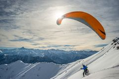 Paraglider launching from snowy slope Stock Photos