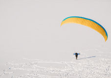 Paraglider. Lonely paraglider on a snowy lake in mountains Stock Image