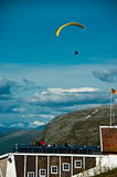 Paraglider in midair. People watching paraglider in midair at event with blue sky and cloudscape background, Tromso, Norway royalty free stock photos