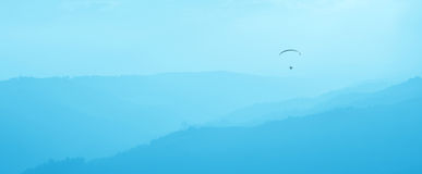 Paraglider in the misty valley Royalty Free Stock Photo