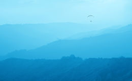 Paraglider in the misty valley Stock Photos