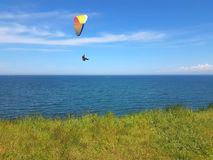 Paraglider near cliff along baltic sea coastline. Adult paraglider near cliff along baltic sea coastline and green meadow wheat field at Boltenhagen Coast royalty free stock images