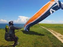 Paraglider near cliff along baltic sea coastline. Adult paraglider wants to start near cliff along baltic sea coastline and green meadow wheat field at royalty free stock photography