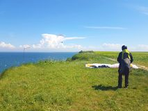 Paraglider near cliff along baltic sea coastline. Adult paraglider wants to start near cliff along baltic sea coastline and green meadow wheat field at stock photo