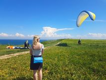 Paraglider near cliff along baltic sea coastline. Woman watching adult paraglider near cliff along baltic sea coastline and green meadow wheat field at stock photography