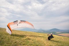 The paraglider opens his parachute before taking off from the mountain in the North Caucasus. Filling the parachute wing. With air before takeoff stock photo