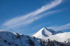 Paraglider ovanför snöig bergmaxima royaltyfri foto