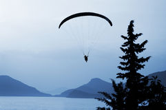 Paraglider over Blue Lagoon. Silhouette of a paraglider making final approach for landing adjacent to the blue lagoon on a warm summer evening. Southern Turkey Royalty Free Stock Photo