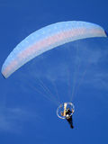 Paraglider over blue sky. Paraglide with motor and propeller Stock Image