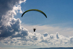 Paraglider over Cornwall, UK. Paraglider above the clouds of St Agnes, Cornwall. Dramatic clouds and blue sky Stock Photo