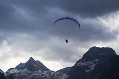 Paraglider over the mountains in Lofer, Austria. Cloudy sky in blue and gray colors Royalty Free Stock Images