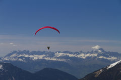 Paraglider over the mountains (red) Royalty Free Stock Photo
