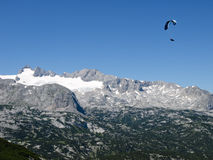 Paraglider over rocks. Paraglider in Austrian Alps above mountains Stock Photography