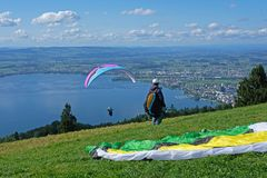 Paraglider over the Zug city, Zugersee and Swiss Alps, Switzerland. Paraglider over the Zug city, Zugersee and Swiss Alps, Zug mountain, Switzerland Stock Photo