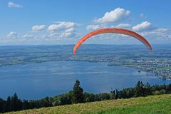 Paraglider over the Zug city, Zugersee and Swiss Alps, Switzerland. Paraglider over the Zug city, Zugersee and Swiss Alps, Zug mountain, Switzerland Stock Image
