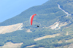 Paraglider or paraplane flying over green velvet hills of Crimean mountains and the Black sea. Stock Photo