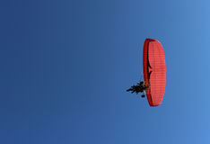 Paraglider and a passenger on a red paraglider with a motor are flying Stock Photography