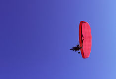 Paraglider and a passenger on a red paraglider with a motor are flying. Royalty Free Stock Photography