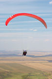 Paraglider pilot. Flying against the blue sky and the earth Stock Image