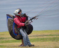 Paraglider Pilot, La Jolla, California. A paraglider, preparing for lift-off with a passenger attached, wearing his helmet and gloves, tightly pulls the multi stock images