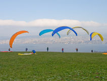 Paraglider pilots at take off. Paragliders pilot play with their wing in the wind royalty free stock photo
