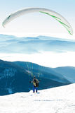Paraglider preparing to get launched from snowy slope of a mountain Stock Images