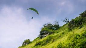 Paraglider que voa fora dos montes gramíneos acima da praia de Gunung Payung, Bali Imagens de Stock