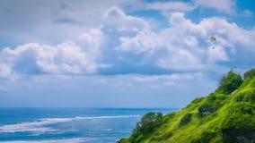 Paraglider que voa fora dos montes gramíneos acima da praia de Gunung Payung em Bali do nordeste um das áreas populares para Foto de Stock Royalty Free