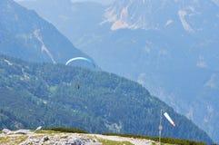 Paraglider que voa sobre o céu com água azul e as montanhas no dia ensolarado brilhante Vista aérea do paraglide imagens de stock