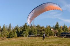 Paraglider is ready to take off over a green hill Stock Image