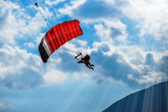 Paraglider with red parachute flying in the blue sky stock photos