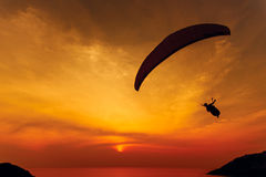 Paraglider silhouette against the background of the sunset sky Stock Photography