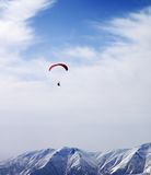 Paraglider silhouette of mountains in windy sky at sun day Stock Photography