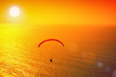 Paraglider. Silhouette of paraglider soaring over sea at sunset Stock Image