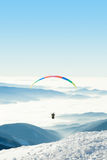 Paraglider in the sky above a snowy mountain top Stock Images