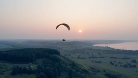 Paraglider in the sky. Airsailing vehicle is drifting above green landscape . Parachute, paragliding comcept. Airsailing vehicle is drifting above green stock video